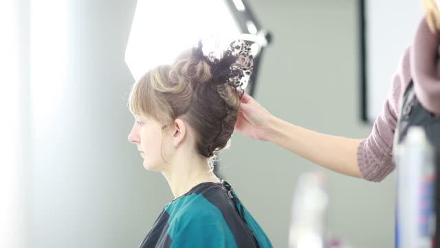 vídeos de stock, filmes e b-roll de mulher ter o cabelo com estilo - coque cabelo para cima