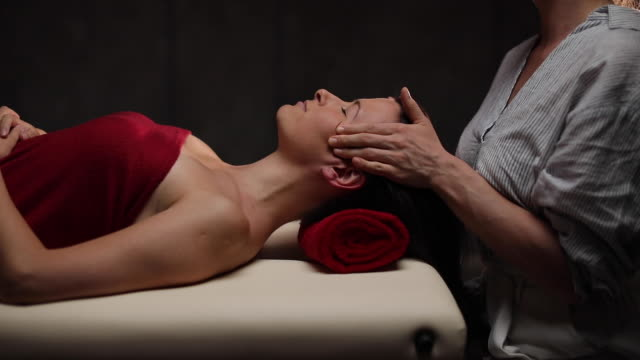 woman getting head and neck massage at spa canter - massage table stock videos & royalty-free footage