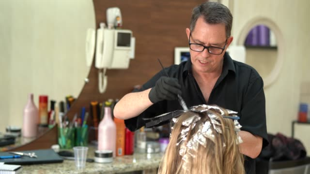 woman getting her hair dyed at salon - hair treatment stock videos and b-roll footage