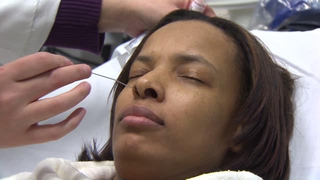 wgn woman getting influenza nasal swab on december 04 2013 in chicago illinois - grippeimpfstoff stock-videos und b-roll-filmmaterial