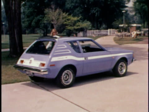 montage pan ws woman getting into blue amc gremlin/ ms women getting into car/ cu seat with levi's brand upholstery / usa - levi's stock videos & royalty-free footage