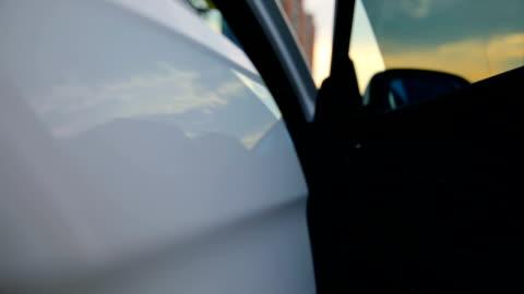 vidéos et rushes de femme monte sur la voiture - entrée
