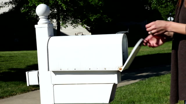 woman getting mail from mailbox - mailbox stock videos and b-roll footage