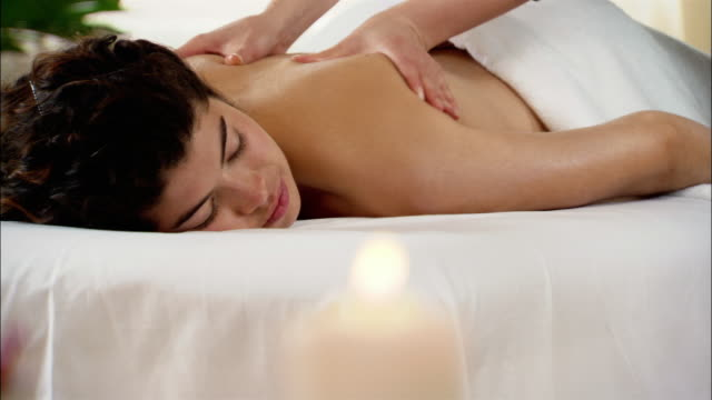 Woman getting massage at spa / tilt up to massage therapist