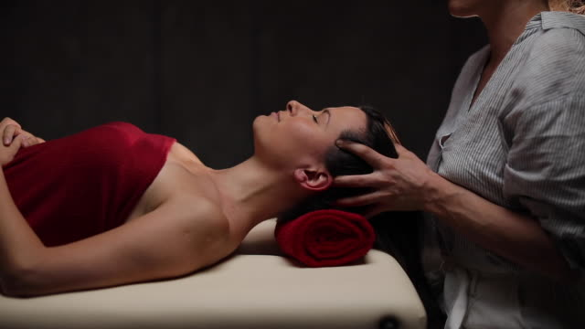 woman getting massage from professional masseuse at spa canter - massage table stock videos & royalty-free footage