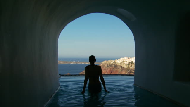 a woman getting out of a luxurious pool - oia santorini stock videos & royalty-free footage
