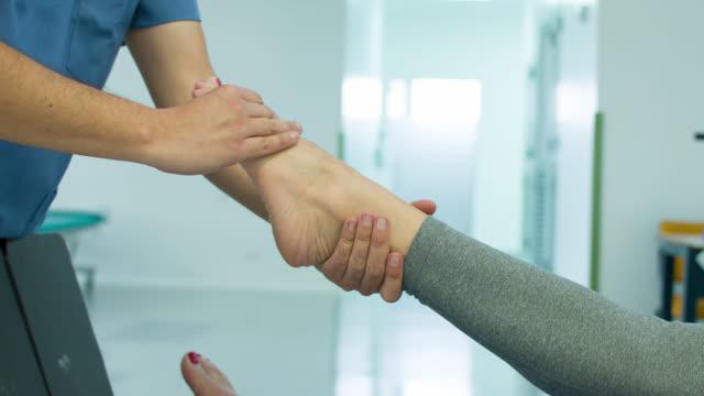 女性彼女の足首の理学療法を取得