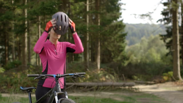 stockvideo's en b-roll-footage met woman getting ready for cycling - sporthelm