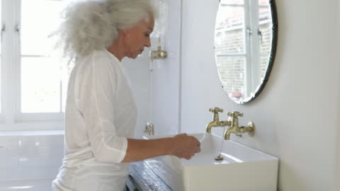 woman getting ready in the bathroom - grey hair stock videos & royalty-free footage