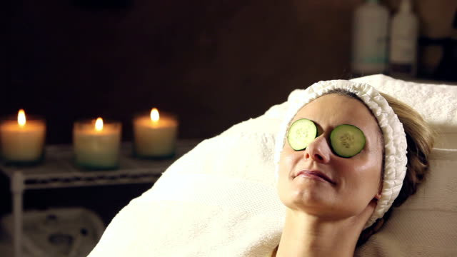 vídeos de stock e filmes b-roll de woman getting spa treatment, cucumbers on eyes - cuidado com o corpo
