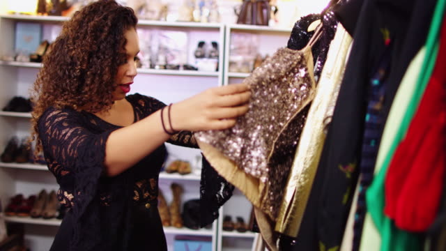 woman getting stuck on sequinned dress in vintage store - second hand stock videos & royalty-free footage