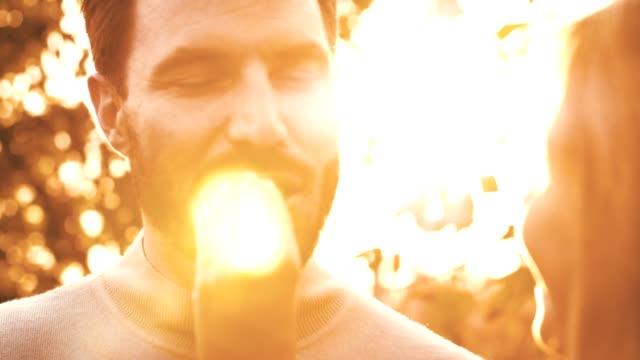 vidéos et rushes de femme donne macaron à un homme à l'extérieur - partage
