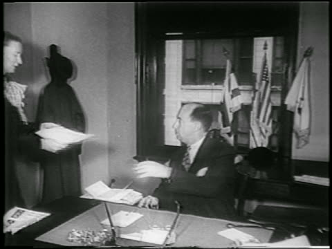 vídeos y material grabado en eventos de stock de woman gives paper to presidential nominee, adlai stevenson, at desk in office / newsreel - 1952