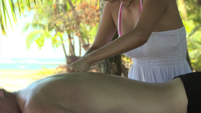 woman giving a man a massage under palm trees