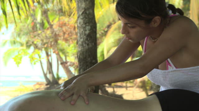 woman giving a man a massage under palm trees - see other clips from this shoot 1157 stock videos & royalty-free footage