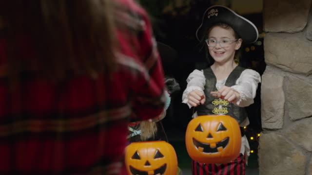 woman giving candy to children wearing costumes on halloween / cedar hills, utah, united states - geben stock-videos und b-roll-filmmaterial