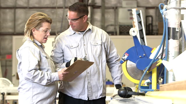 Woman giving direction to man with table saw in factory