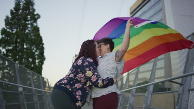 woman giving her partner a kiss under the pride flag - bisexuality stock videos and b-roll footage