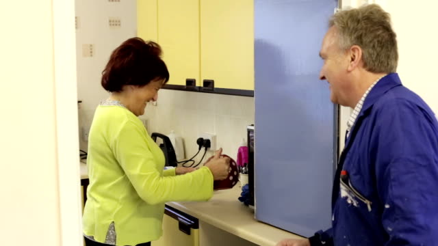 woman giving plumber a cup of tea in a community centre - plumber stock videos & royalty-free footage