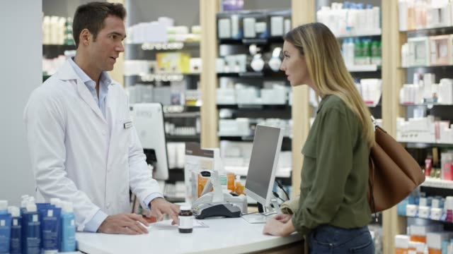 woman giving prescription medicine to chemist - pharmacy stock videos & royalty-free footage