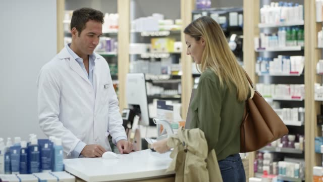 woman giving prescription to male chemist - selling stock videos & royalty-free footage