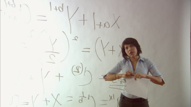 ms woman giving satisfied look to completed math equation written on glass/ new york city - complexity stock videos & royalty-free footage