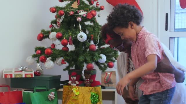vídeos y material grabado en eventos de stock de mujer dando a su nieto un regalo de navidad - regalo de navidad