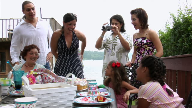 woman giving young girl present at her birthday party as man films home movies with digital camcorder / new jersey - digital camcorder stock videos & royalty-free footage