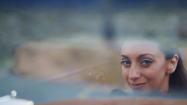 ecu. woman glances in rearview mirror and smiles as she drives on scenic road trip. - 40 44 years stock videos & royalty-free footage