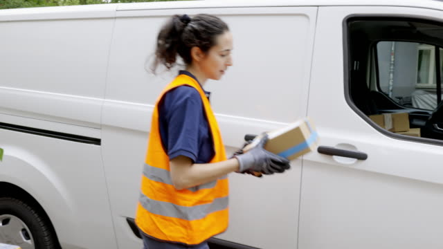 woman goes on delivering postal parcel - van stock videos & royalty-free footage