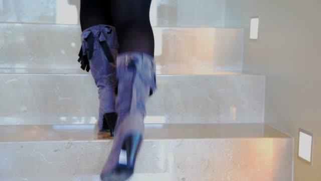 woman goes up and down on staircase - trappsteg och trappor bildbanksvideor och videomaterial från bakom kulisserna