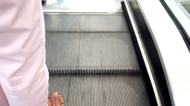 woman going on escalator upstairs - slipper stock videos and b-roll footage