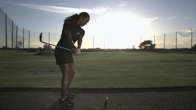 Woman golfer hitting an iron on a range in Slow Motion