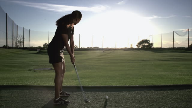 Woman golfer hitting an iron on the driving range