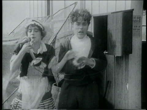 stockvideo's en b-roll-footage met b/w 1915 woman grabbing telephone from man talking into it - 1915