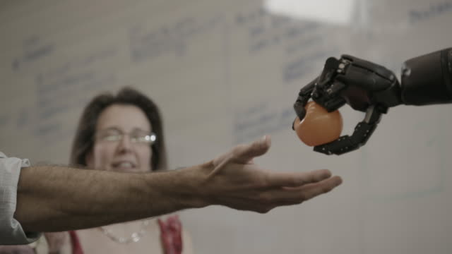Woman grabs ball with bionic hand