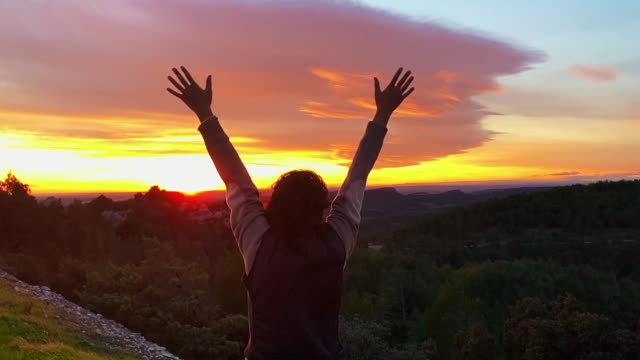 woman greeting the sunset with arms raised in a windy day - hand raised stock videos & royalty-free footage
