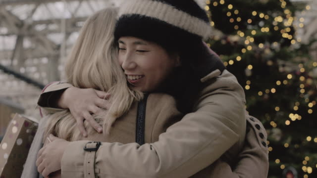 Woman greets and embraces her friend at the rail road station, during the christmas period.
