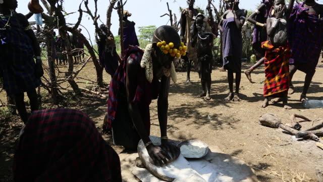 vídeos de stock e filmes b-roll de woman grinding flour with stones in murzy tradition vilage omo valley ethiopia - corno de áfrica