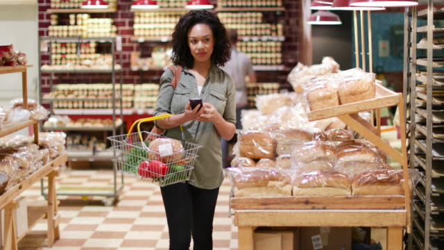 woman grocery shopping and using smartphone - zusammenstellung stock-videos und b-roll-filmmaterial
