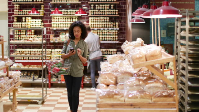 Woman grocery shopping and using smartphone