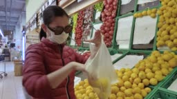 Woman grocery shopping at supermarket with N95 face mask