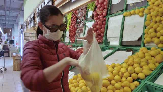 woman grocery shopping at supermarket with n95 face mask - citrus fruit stock videos & royalty-free footage