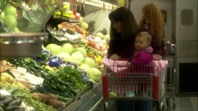a woman grocery shops with a child in her cart. - albuquerque new mexico stock videos & royalty-free footage