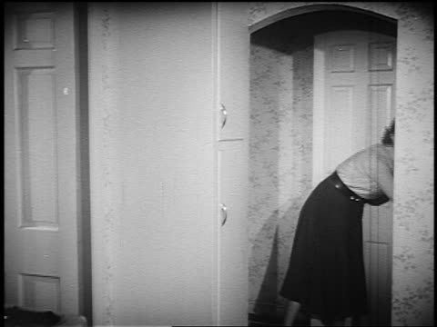 b/w 1951 woman guiding boy thru doorway to bomb shelter in house / man approaches with girl - yorkville illinois stock videos & royalty-free footage
