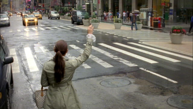 ms woman hailing and getting in to cab, new york city, new york, usa - arme hoch stock-videos und b-roll-filmmaterial