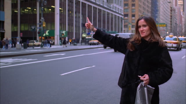 A woman hails a cab on a New York City street. Available in HD.