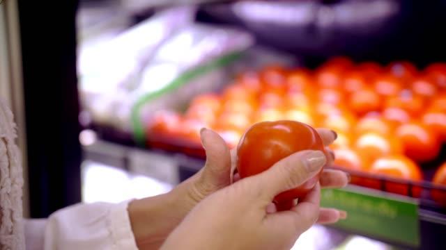 vídeos de stock, filmes e b-roll de cu: mão de mulher escolher um vegetal em minimercado - tomato