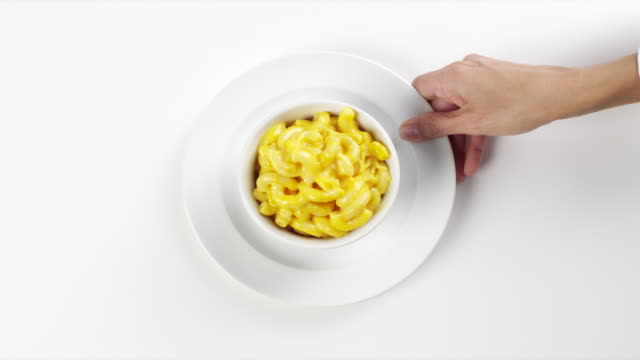 CU Woman hand entering setting down round white bowl with macaroni and cheese / Omaha, Nebraska, United States