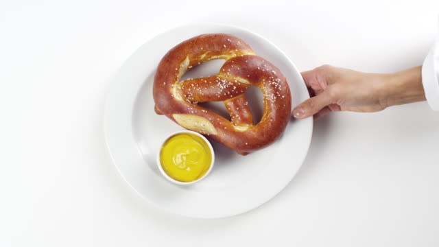 cu woman hand entering setting down round white plate with big huge pretzel with yellow mustard / omaha, nebraska, united states - teller stock-videos und b-roll-filmmaterial